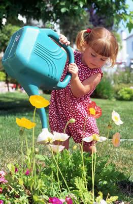 little girl in a sundress watering flowers