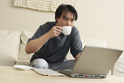 man on couch working on laptop & drinking coffee