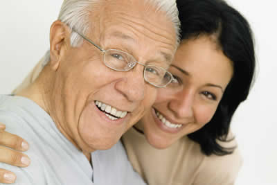 Elderly man with younger woman smiling