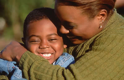 Little boy being embraced by his mother (african-american)