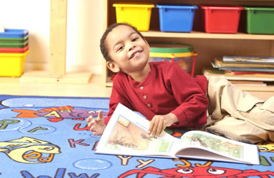 Boy reading happily in school